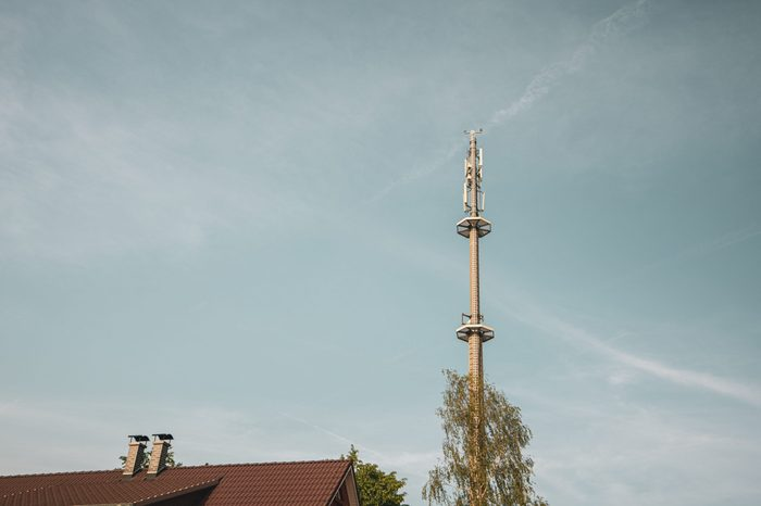 a radio mast for the mobile phone network towers above a residential building into the blue sky in a residential area