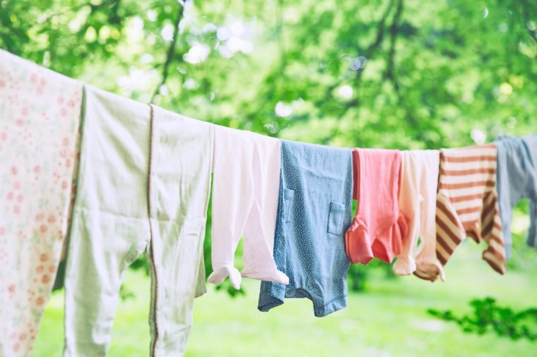 Baby cute clothes hanging on the clothesline outdoor. Child laundry hanging on line in garden on green background. Baby accessories.