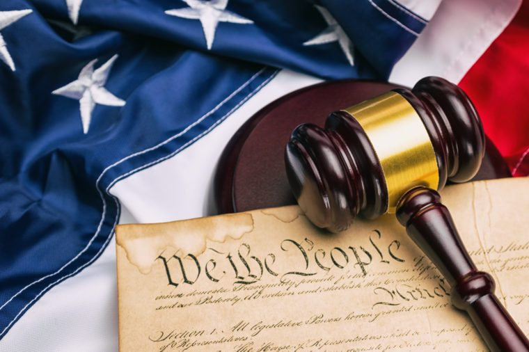 American flag with US constitution and a judge's gavel symbolizing the American justice system or the Judicial Branch of government