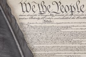 Close crop of the preamble to the United State's Constitution with an eagle feather pen.