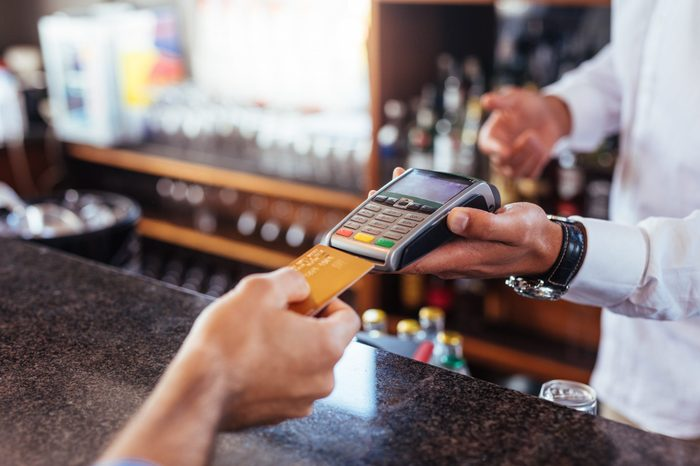 Customer making payment using credit card. Close up of card payment being made between customer and bartender in cafe.
