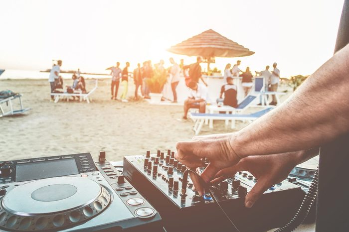 Dj mixing at sunset beach party in summer vacation outdoor - Disc jockey hands playing music for tourist people in chiringuito kiosk bar - Event, music and fun concept - Focus on left hand