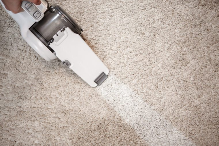 Top view of cordless handheld vacuum cleaner on beige carpet