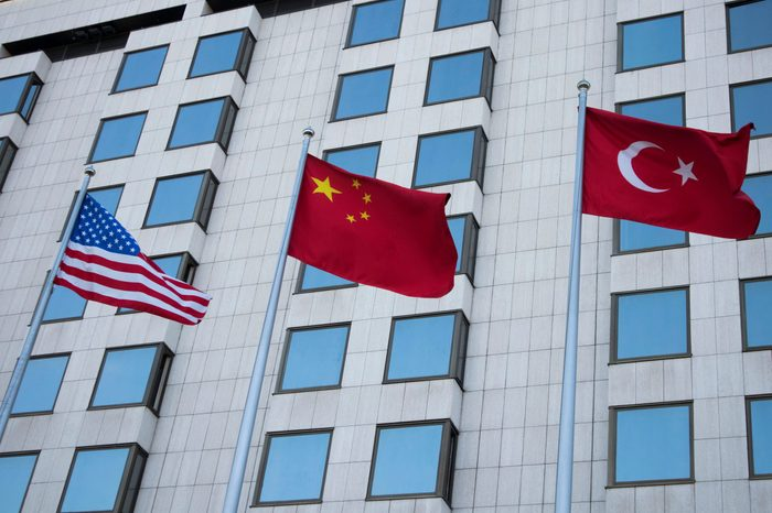 flags of America, China and Turkey on the background of the business building