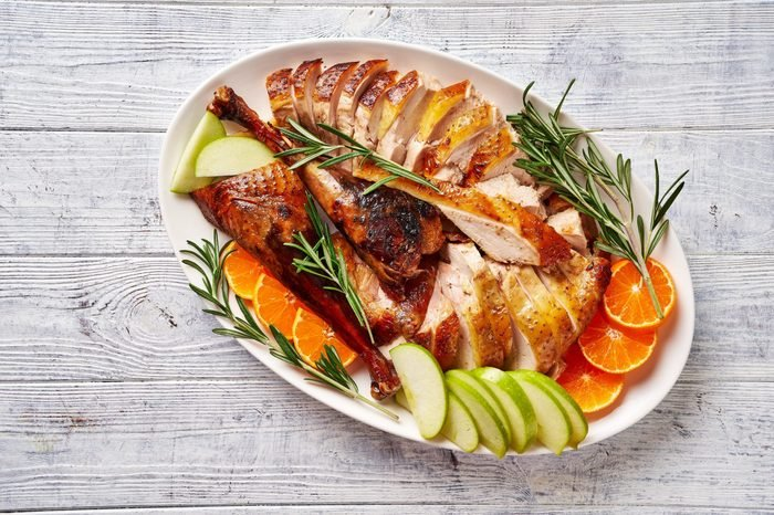 View from above on sliced roast duck served with rosemary, green apple, orange on a white plate on a white wooden table, close-up