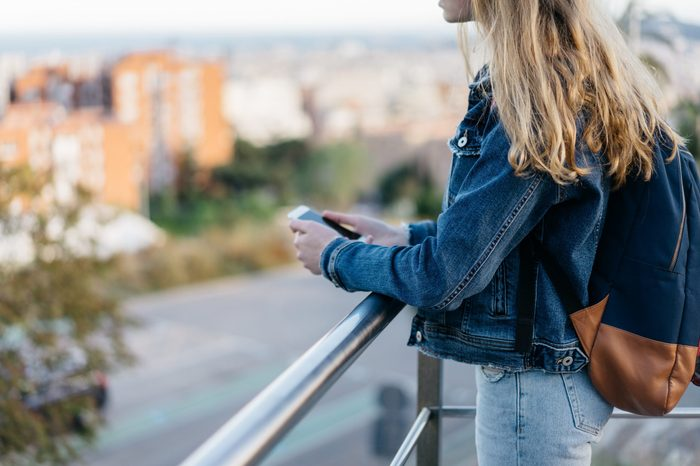 young millennial girl in a jeans jacket use smartphone, city blurring on background, space for text. woman texts to a friend. teenager with a gadget. technology and people. place for logo