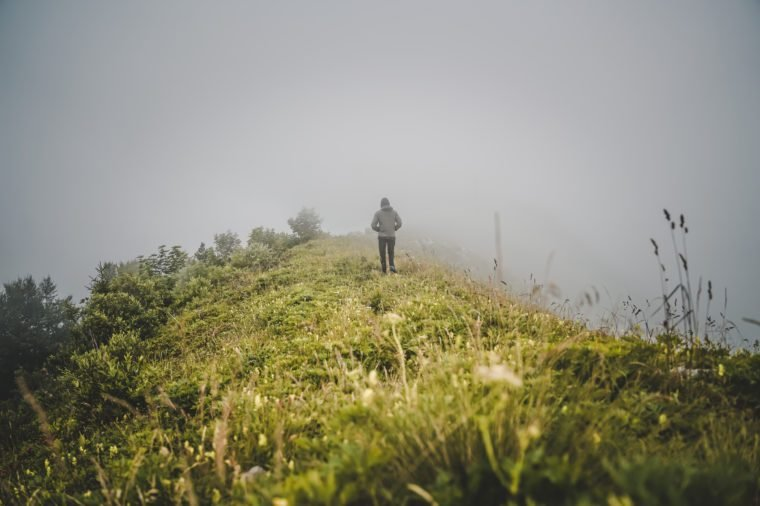Person walking alone into the fog, young men disappearing in the clouds