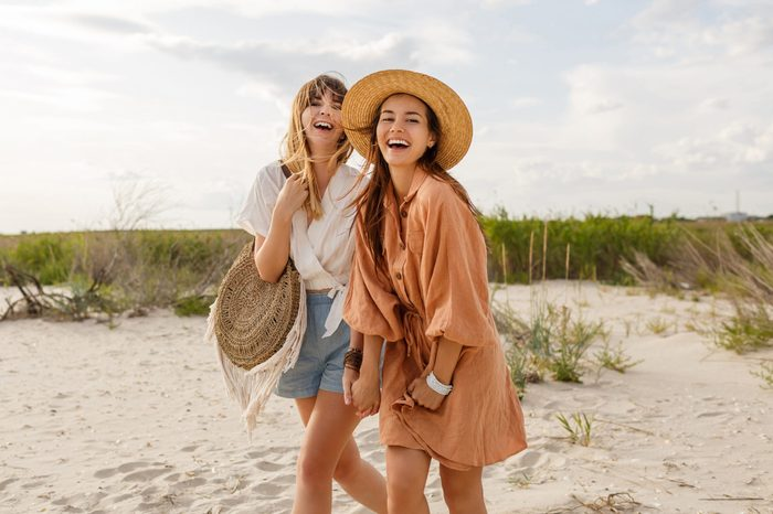 Two pretty sister girls posing on the beach, vacation mood, crazy positive feeling, summer trendy clothes and straw hat.