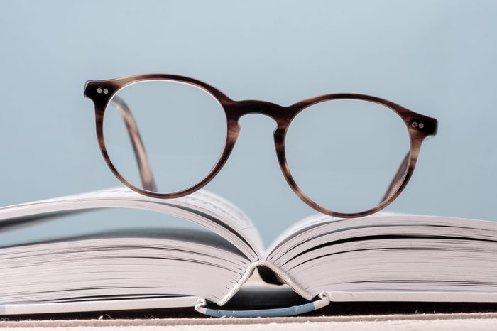 Reading eyeglasses on open book close-up