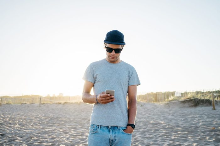 fit young attractive man in a gray casual t-shirt holds mobile phone. picture of male using white smartphone on the beach during beautiful sun light at the holidays. close up of a person touch screen