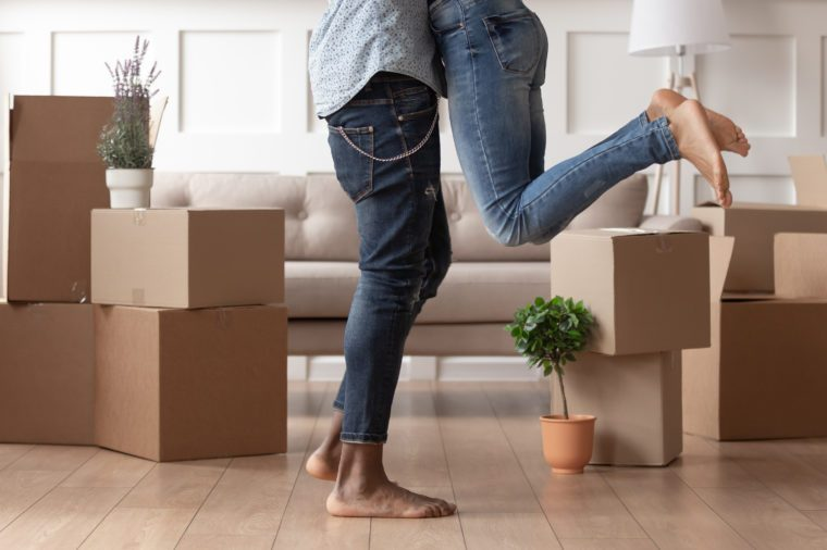 Close up young husband in jeans lift wife surrounded by cardboard boxes excited to move in new flat, happy african American couple have fun hug feel euphoric relocating together to own house