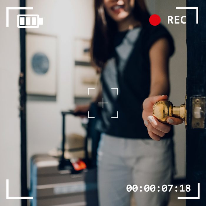 woman opening door holding suitcase with camera viewfinder overlay