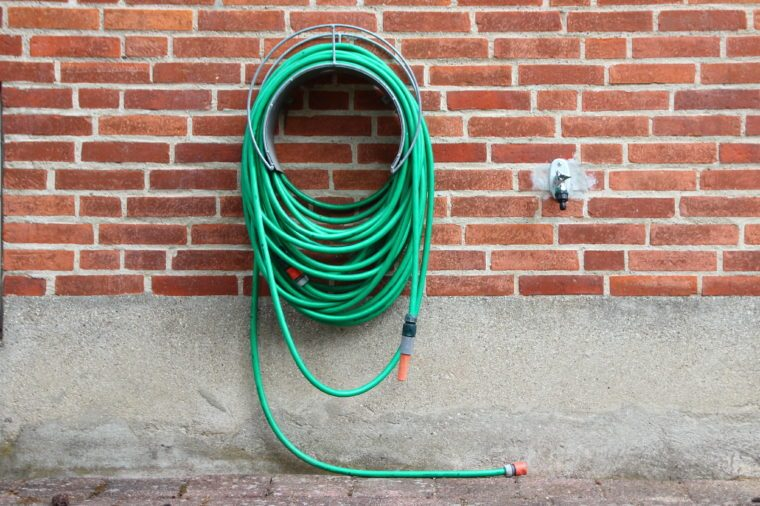 Green Garden Water Hose Hanging on Red Brick wall. Not connected to Water Tap.