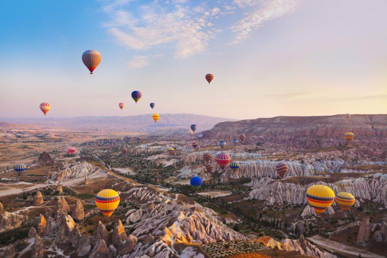 Horkovzdušný balón lietajúci nad skalnou krajinou v Kappadokii v Turecku