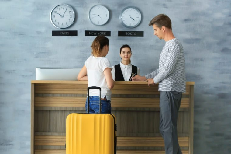 Young couple at reception desk in hotel