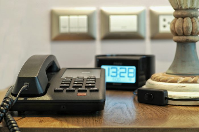 Hotel room telephone with digital clock on background on beside table. Concept for travel or business.