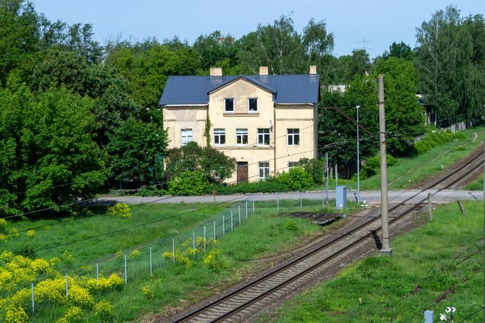 House near train rails and iron crossing. House with green trees and yellow flower
