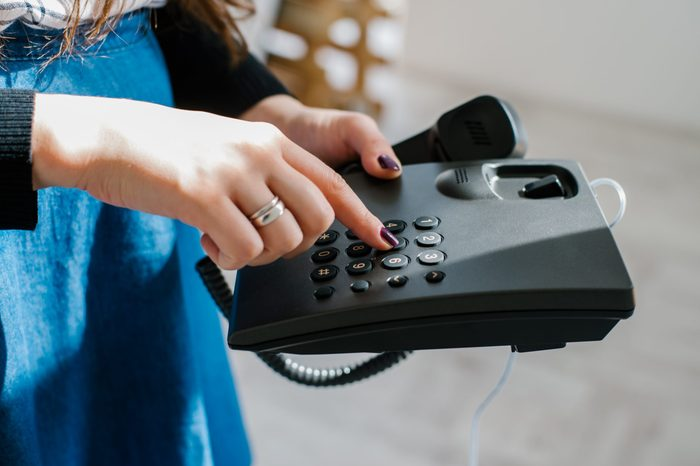 beautiful young brunette woman holding office or home phone