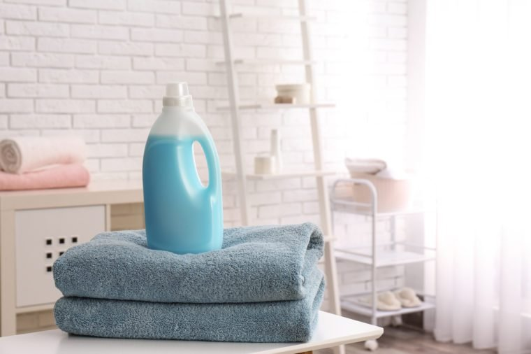 Bottle of detergent and clean towels on table indoors, space for text. Laundry day