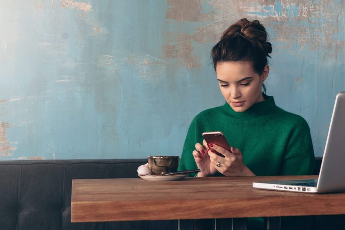 Young smiling business woman sitting at table in cafe and using smartphone. On table is laptop and cup of coffee.Student learning online. Girl shopping online, checking email,blogging, chatting.