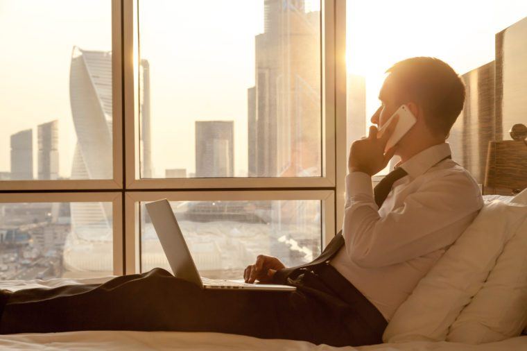 Handsome young businessman wearing formal white shirt and tie sitting on the bed with laptop in modern room. Self-employed person using smartphone in penthouse and looking at sunny city view in window