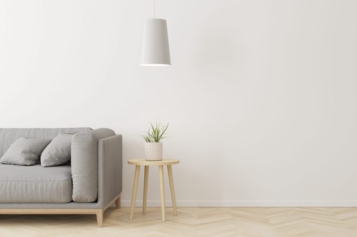 Interior of living room modern style with grey fabric sofa,wooden side table and white ceiling lamp on wooden floor.