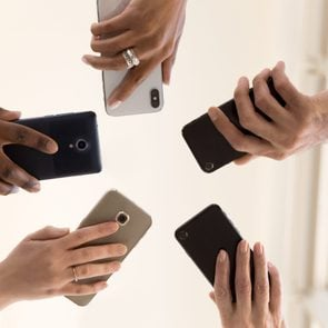 Male and female diverse hands holding cell phones, multiracial business people using smartphones applications software, users and devices concept, mobile communication, close up below bottom view