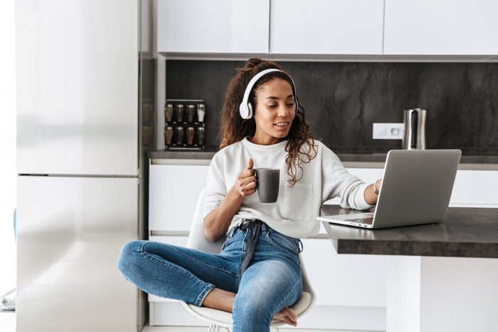 Image of modern african american girl wearing headphones using laptop while sitting in bright kitchen
