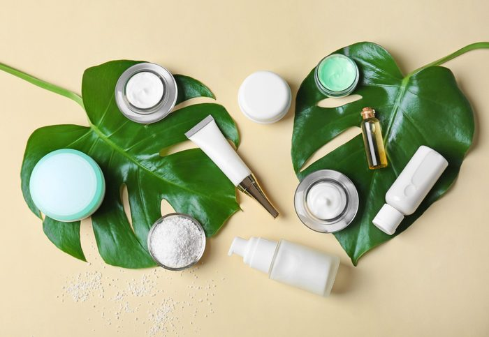 Natural cosmetics and leaves on light background