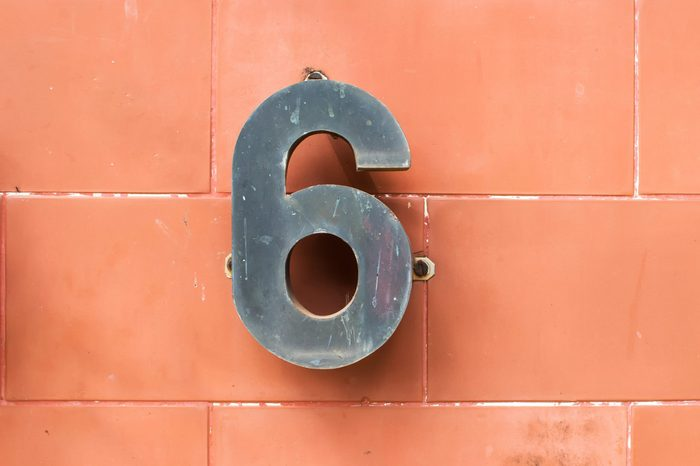 house number six. Decorative black lettering on a brick wall
