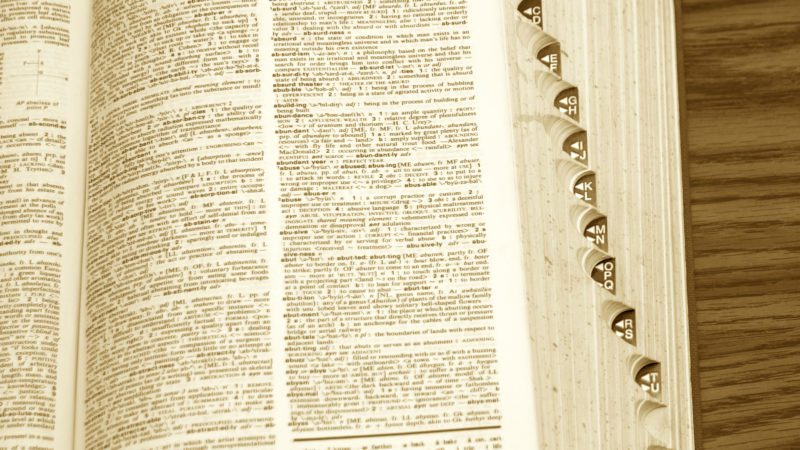 old dictionary with page open, showing side tabs on desk in sepia