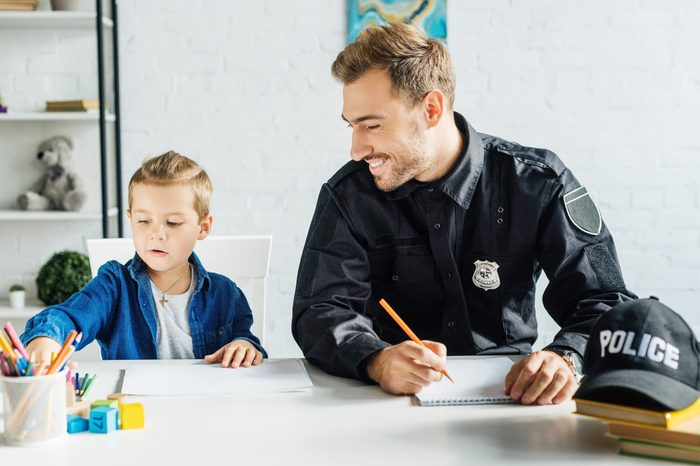 happy young father in police uniform and his little son drawing together at home