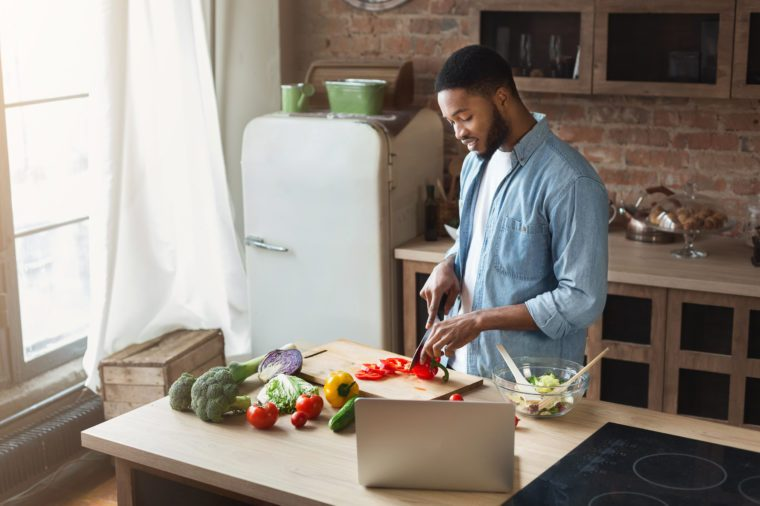 African-american man preparing vegetable salad in loft kitchen