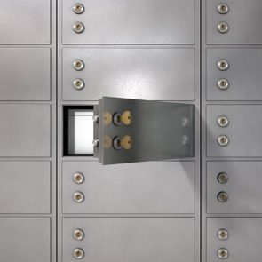 A closeup of a wall of closed metal safety deposit boxes with one open revealing its contents inside