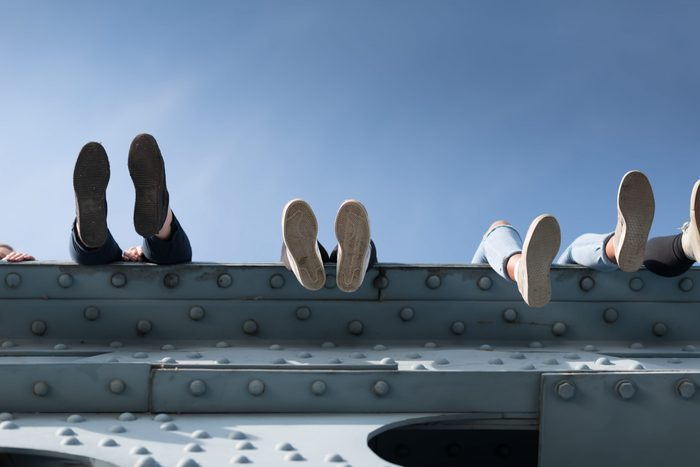 Children sit on a high bridge. Photo below. you can See the soles of their shoes. A very dangerous pastime. The opportunity to earn a fall and injury. Moscow, Gorky park