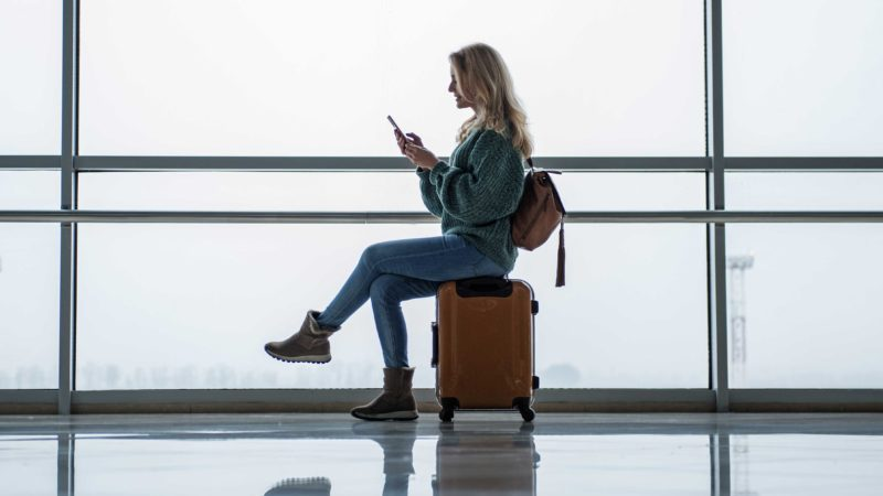 Side view of young woman waiting for the flight at the airport. She is sitting on suitcase and holding cellphone. Copy space in left side
