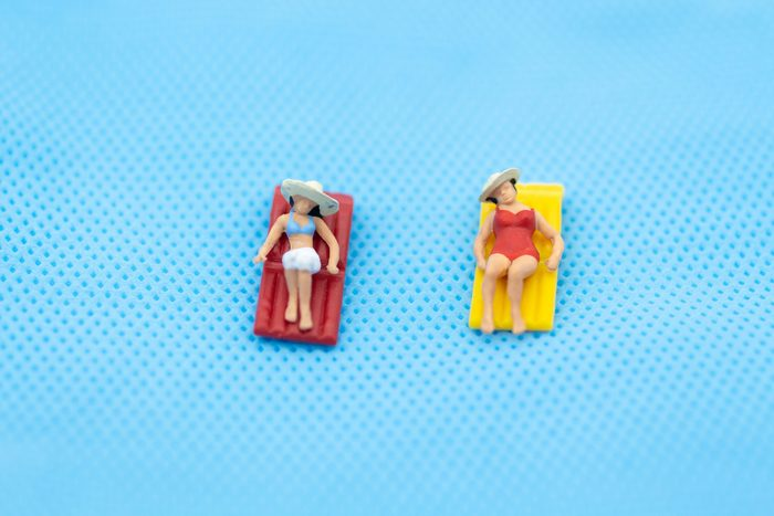 miniature woman wearing swimsuit relaxing on the beach at the sea. Image use for travel business concept. lie vs lay