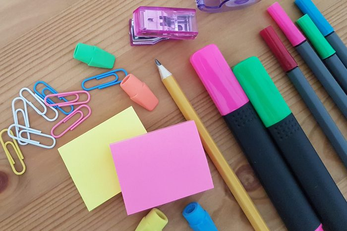 Colored pencils, paper clips, markers, and notepads laying on a wooden table, School supplies, Office supplies, Back to school