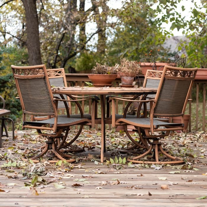 Summer season is over. Garden furniture covered in falling leaves.