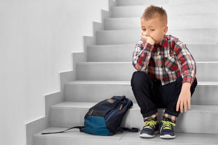 Handsome, thoughtful schoolboy sitting on stairwell in school, leaning head on hand. Lonely, sad, depressed child in checked shirt, jeans and sneakers thinking.