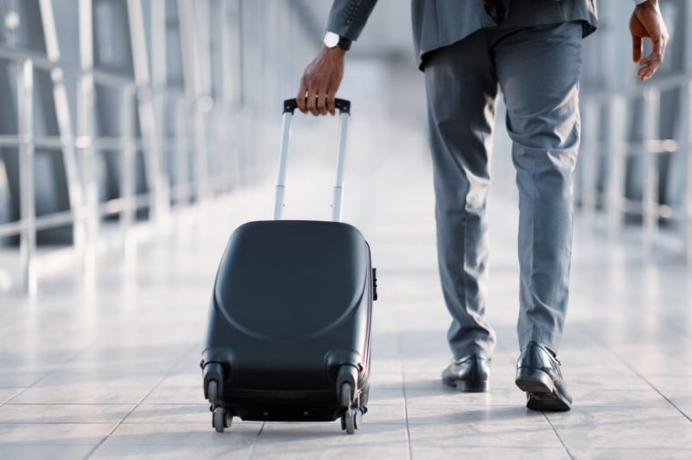 Businessman At Airport Moving To Terminal Gate For Business Trip, Back View