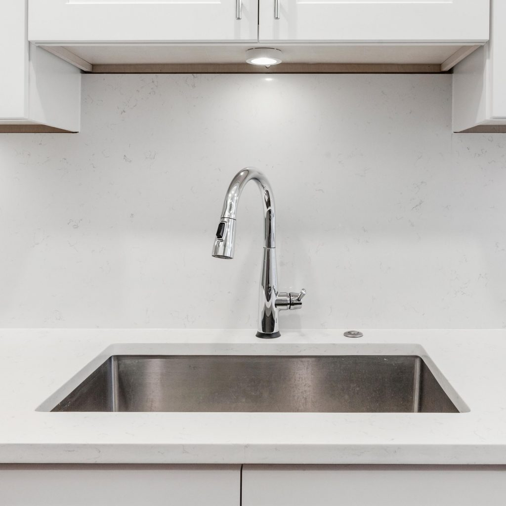 White kitchen built with shaker style cabinets and white granite. Shows stainless dishwasher, granite back splash. Brushed chrome faucet and hardware