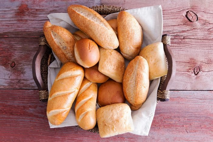 Assorted crusty fresh golden bread rolls in a basket in different specialty shapes displayed on a rustic wooden buffet table as an accompaniment to a meal