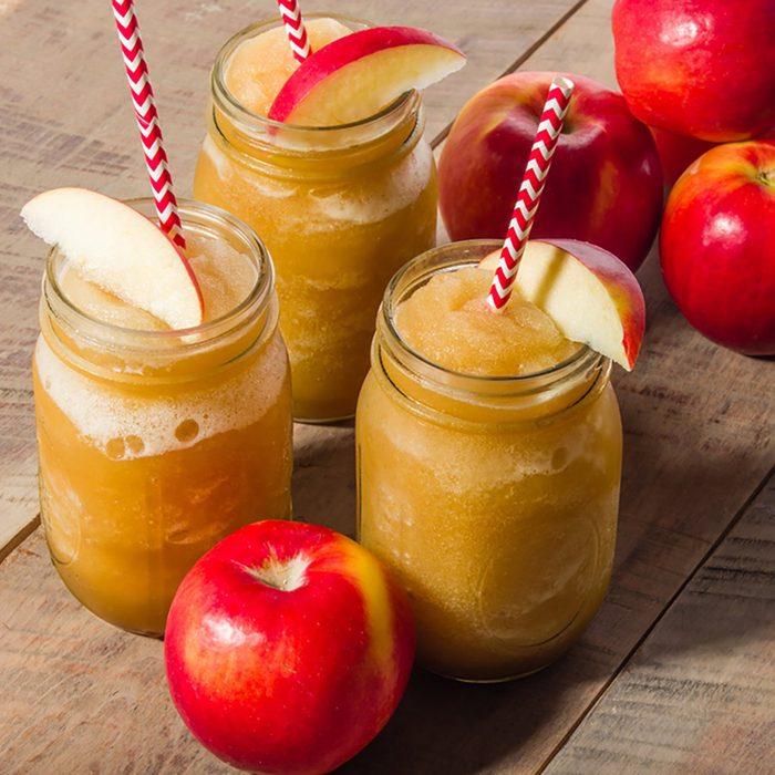 Red apples with frozen apple slushy drink in mason jar