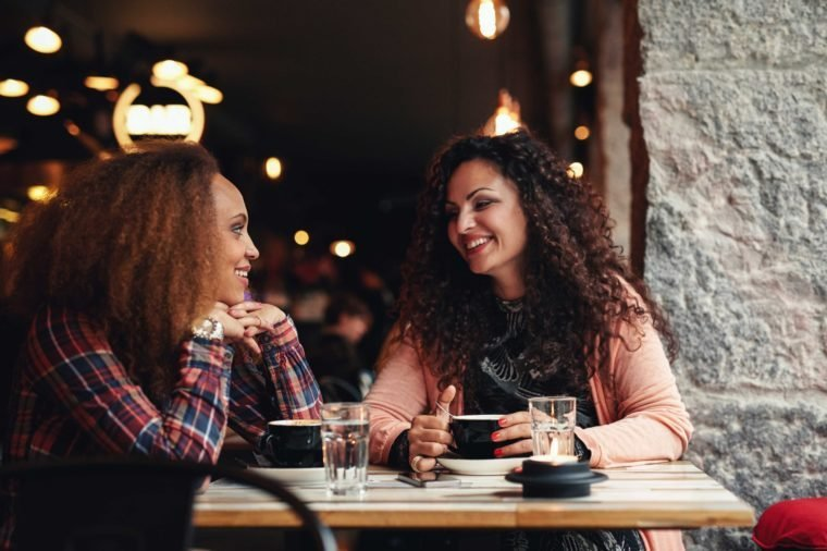 Two women discussing at a restaurant smiling. Young friends sitting in a cafe and talking.