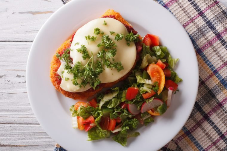 Italian chicken Parmigiana and fresh vegetable salad close up on a plate on the table. horizontaltop view