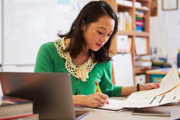 Female Asian teacher at her desk marking studentsâ?? work