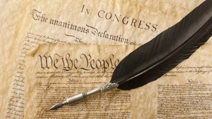 The Constitution for the United States of America with a quill pen