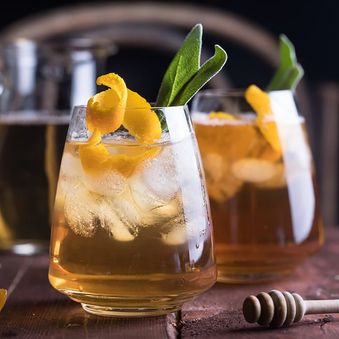 Refreshing iced tea with whiskey, honey, citron and sage on rustic wooden background