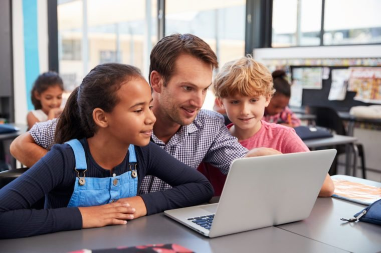 Teacher and two young students use laptop computer in class
